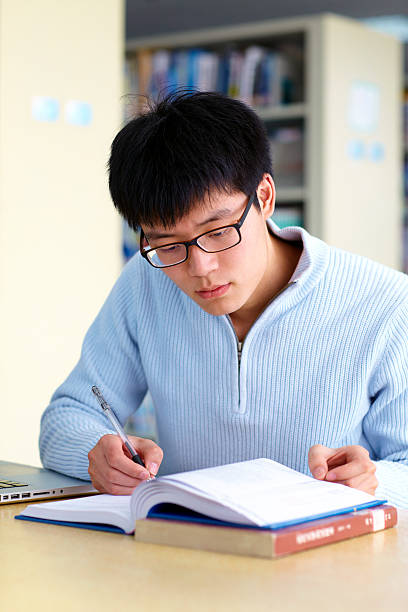 young man study in library stock photo