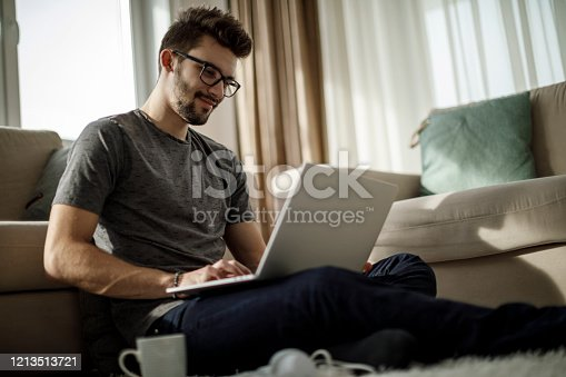 Young man studying and working on laptop at home