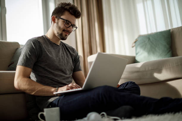 Young man studying and working on laptop at home stock photo