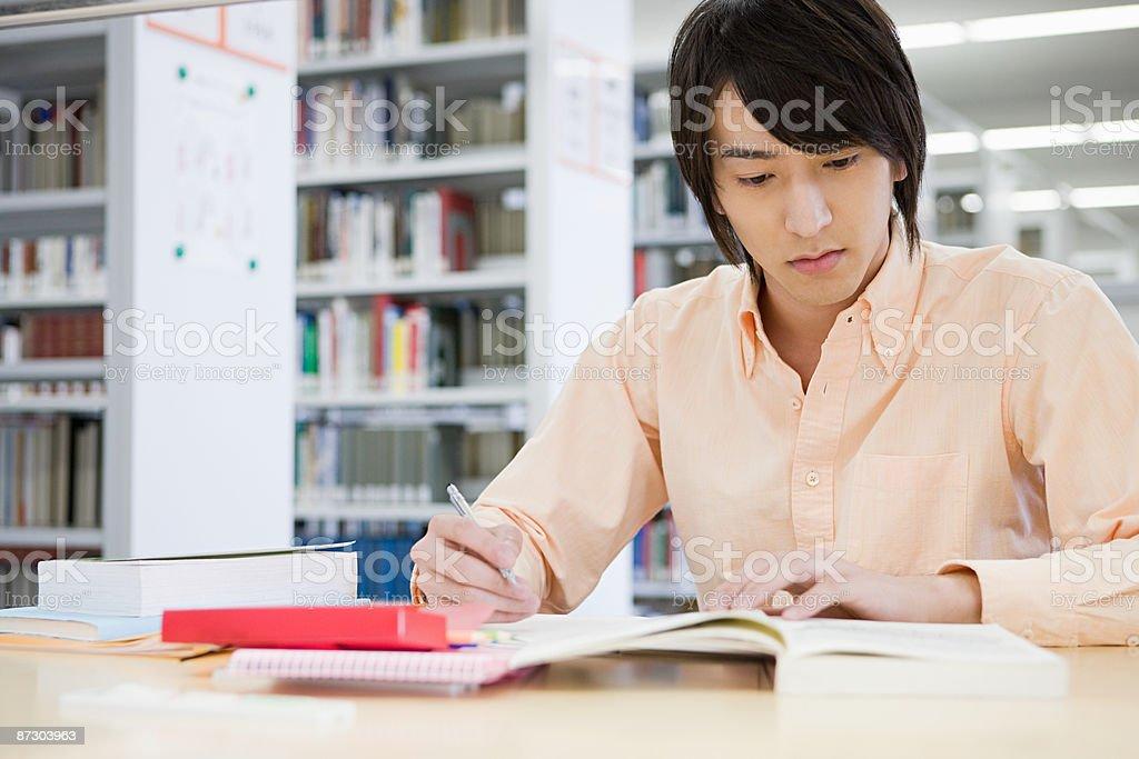 Joven estudiando en la biblioteca - foto de stock