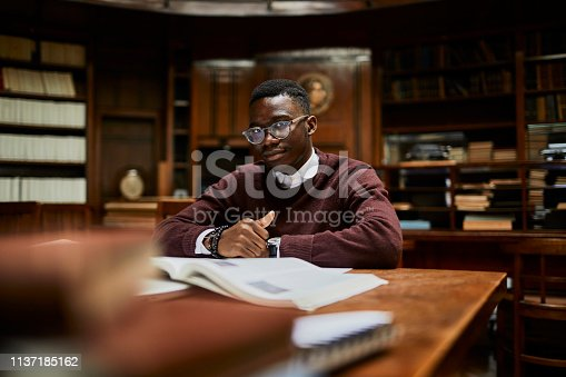 Close up of a young man studying in a library