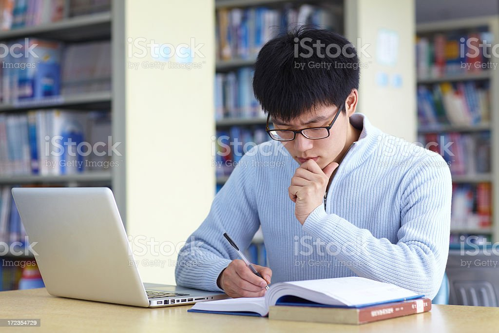 A young man studying with laptop and books royalty-free stock photo