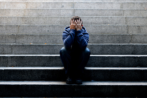 istock Young man suffering depression sitting on ground street concrete stairs 515174319