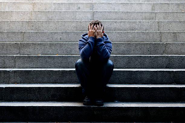 Junger Mann, die unter Depressionen sitzen auf Boden Straße Beton Treppe – Foto