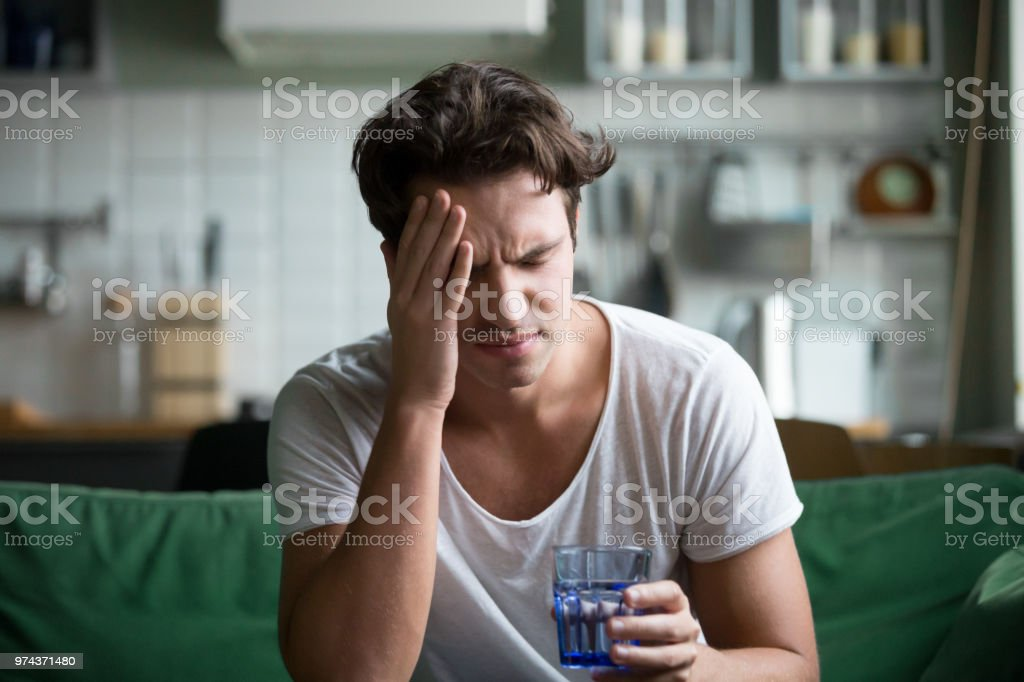 Young man suffering from headache, migraine or hangover at home stock photo