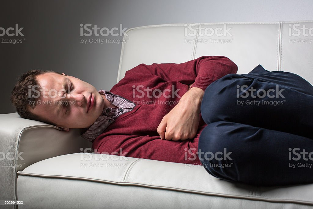 Young man suffering from severe belly pain stock photo