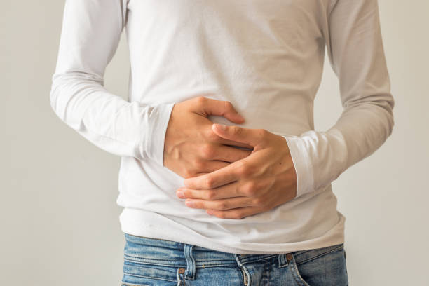 Young man suffering from stomach ache, diarrhea, constipation, acid reflux, indigestion, nausea stock photo