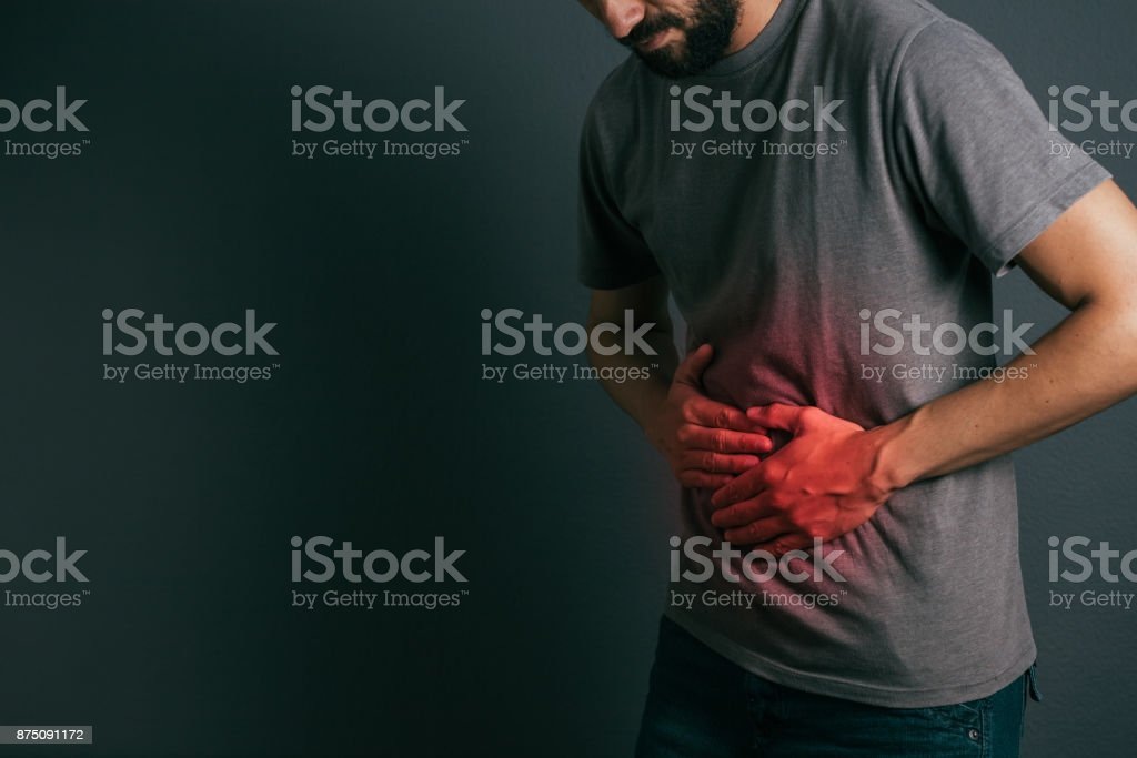 Jovem sofre de pé dor de estômago - Foto de stock de Abdome royalty-free