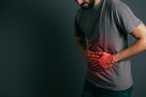 istock Young man suffering from stomach ache standing 875091172