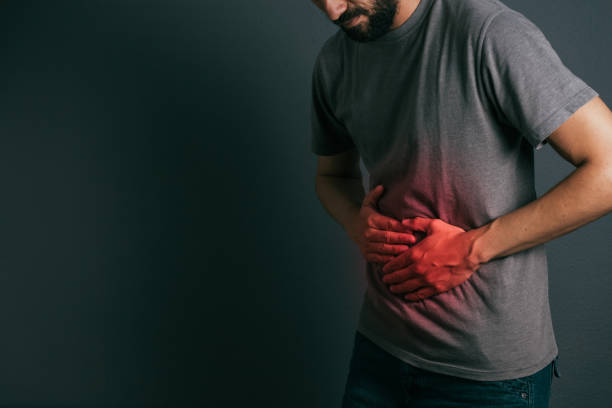 Young man suffering from stomach ache standing stock photo