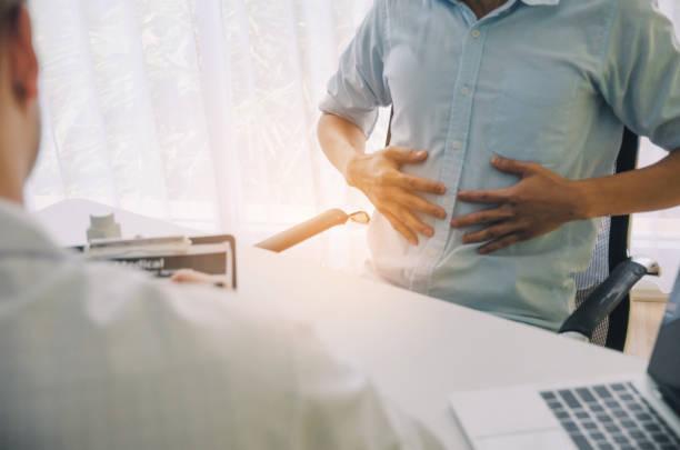 jovem sofre de dor de estômago encontrar médico prescrevendo receita na área de transferência com o laptop na mesa num hospital, síndrome de escritório, cuidados de saúde, médicos, medicina, conceito de farmácia - abdome - fotografias e filmes do acervo