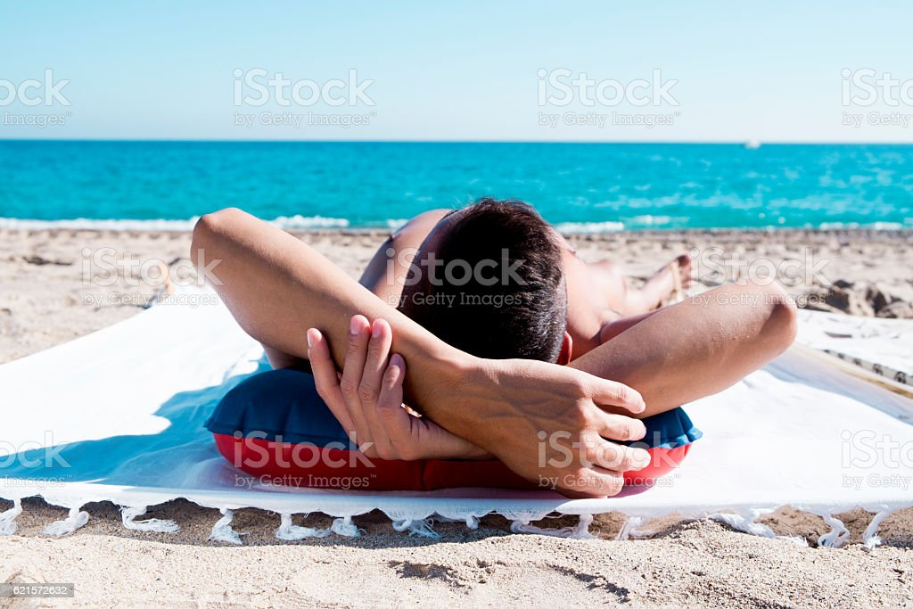 young man sun tanning on the beach photo libre de droits