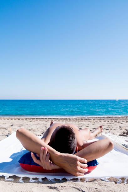 junger mann sonnenbaden am strand - fkk strand stock-fotos und bilder
