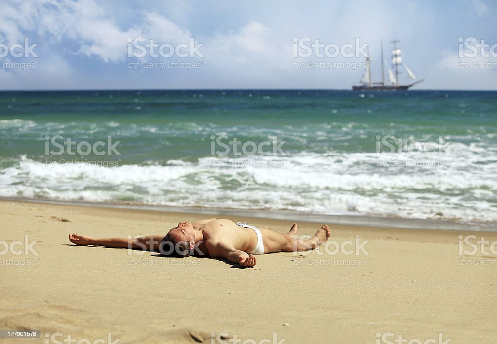 Young man sunbathing at a beach royalty-free stock photo