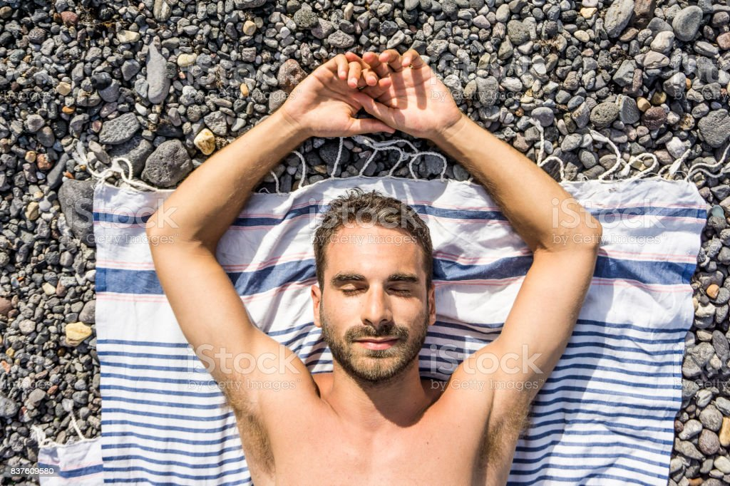 Young man sunbathing on a beach of stones stock photo