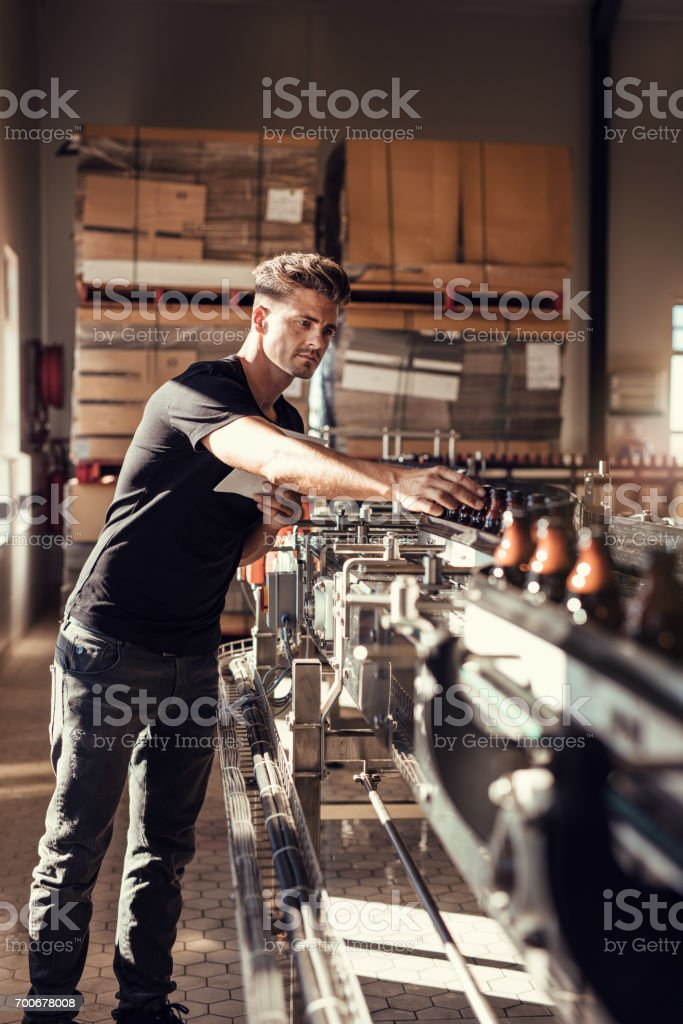 Young man supervising the beer bottling process stock photo