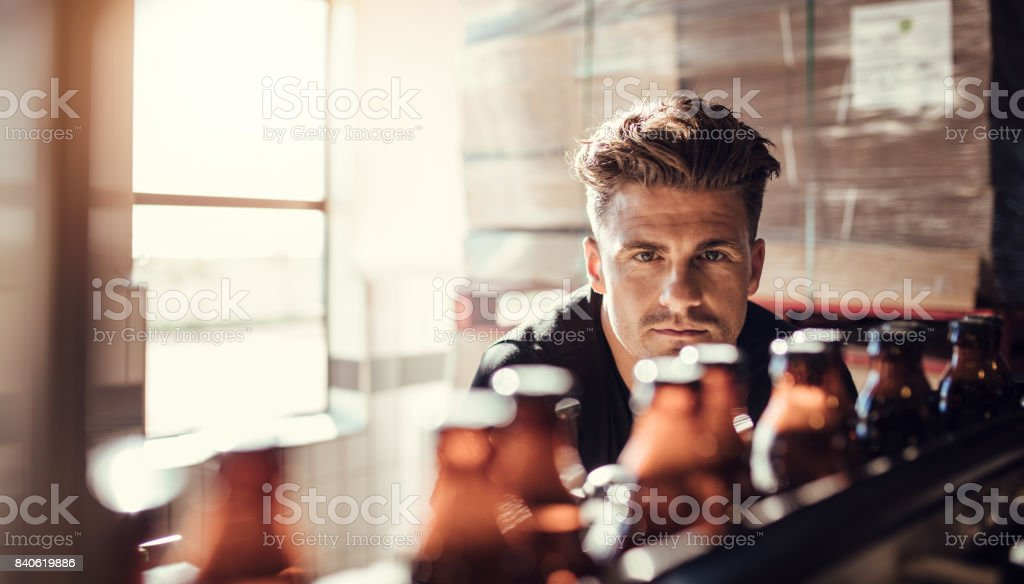 Young man supervising the process of beer bottling stock photo
