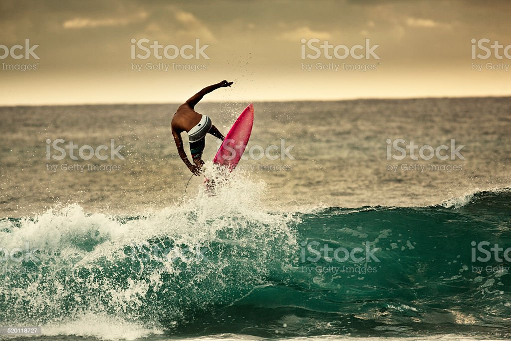 Young Man Surfer Surfing in the Beach of Kauai Hawaii stock photo