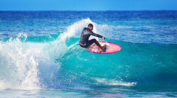 young man surfer surfing in the beach of kauai, hawaii - surfing stock photos and pictures
