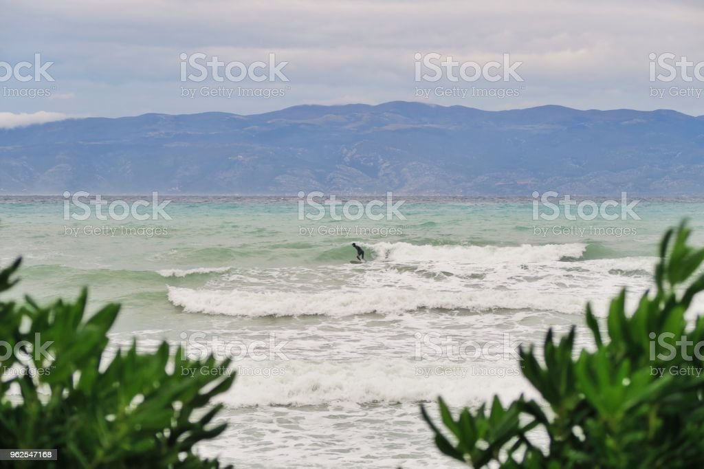 Young man surfing Adriatic sea / Mediterranean sea waves / cold water - Royalty-free Absence Stock Photo