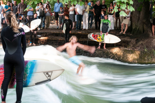 Young man surfing at the Eisbach river in Munich, Germany