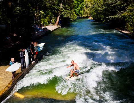Young man surfing at the Eisbach river in Munich Germany