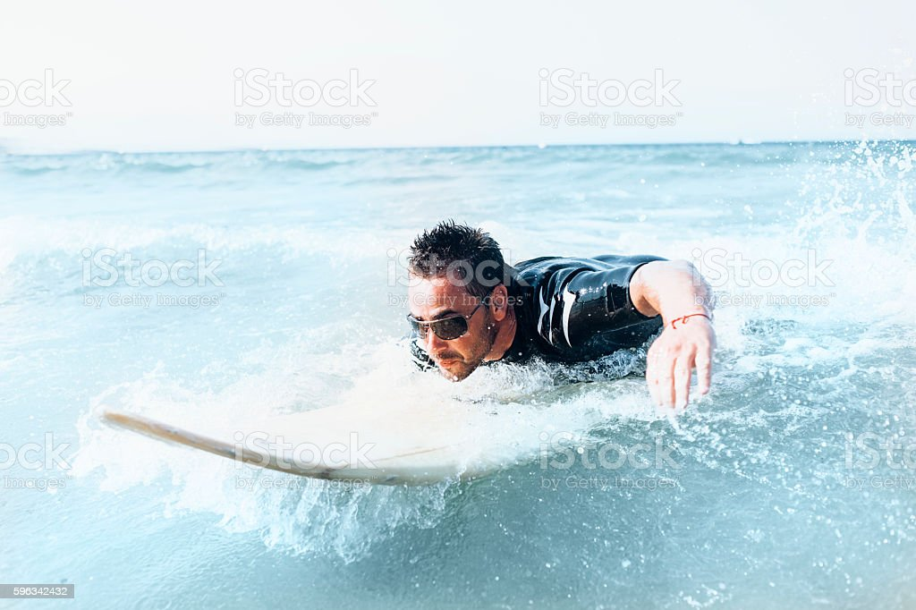 Young man surfing in the sea royalty-free stock photo