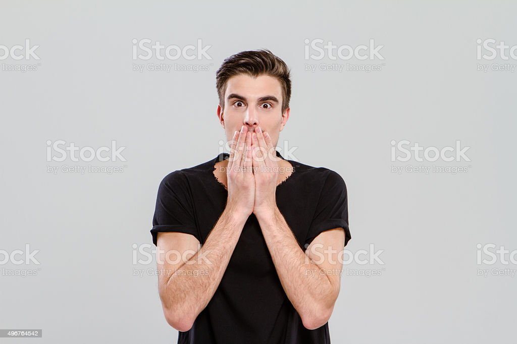 Young man surprised and closed mouth with hands stock photo
