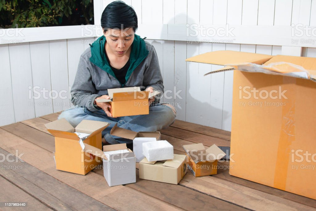 Young man surprised opening box and looking inside and unpacking the...