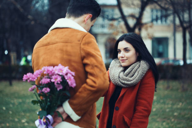Young man surprising his girlfriend on Valentine's day stock photo