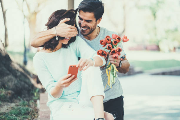 Young man surprising his girlfriend with bouquet of tulips stock photo
