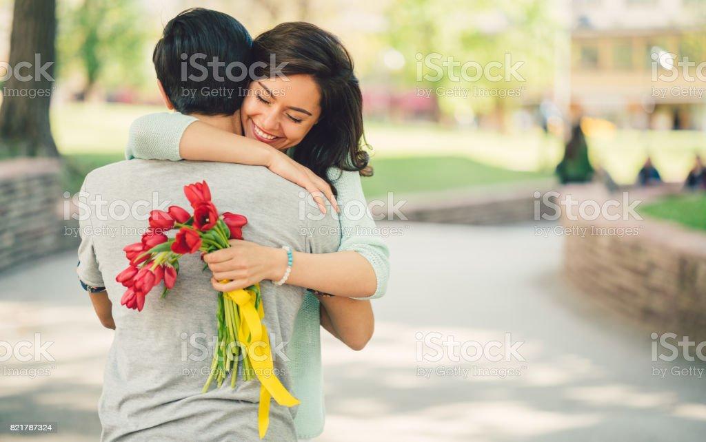 Jeune homme surprenant sa copine avec bouquet de tulipes - Photo