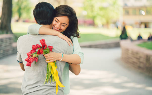 young man surprising his girlfriend with bouquet of tulips - welcome march stock photos and pictures