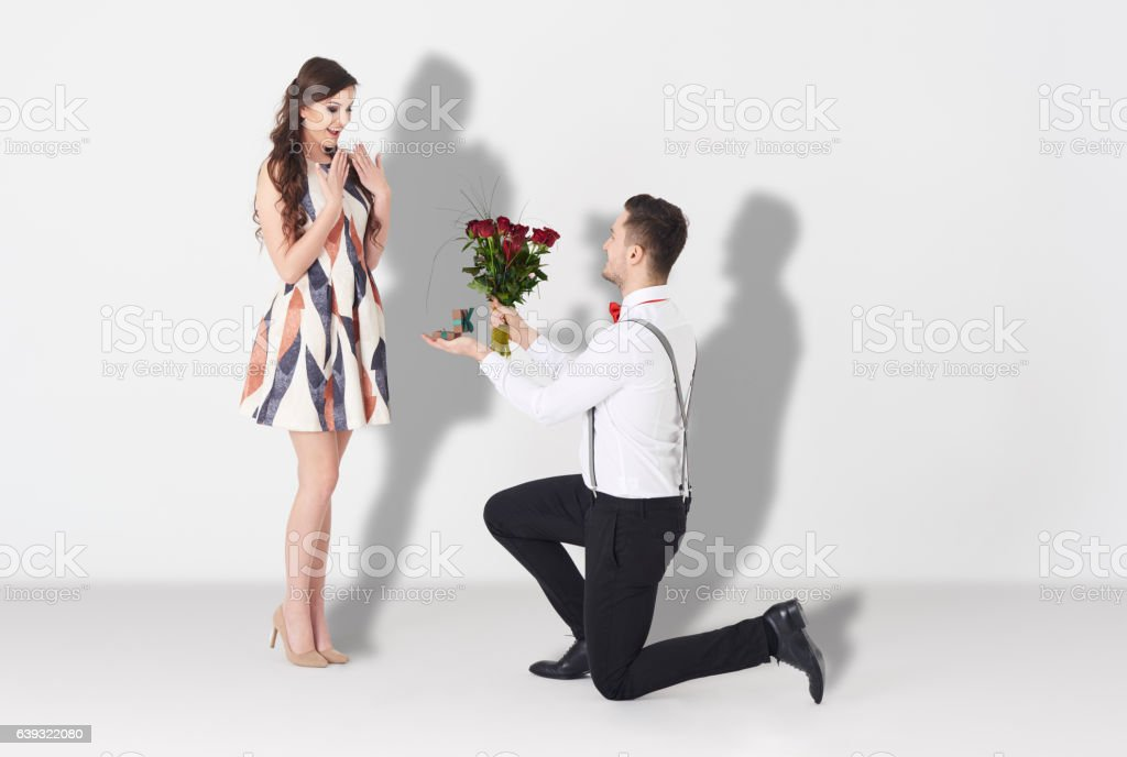 Young man surprising woman with engagement stock photo