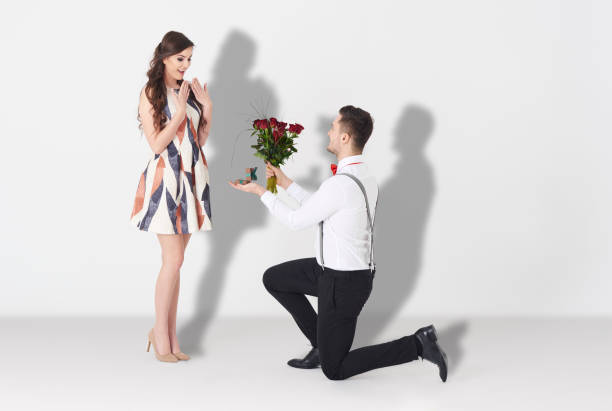 young man surprising woman with engagement - cluster verlobungsringe stock-fotos und bilder