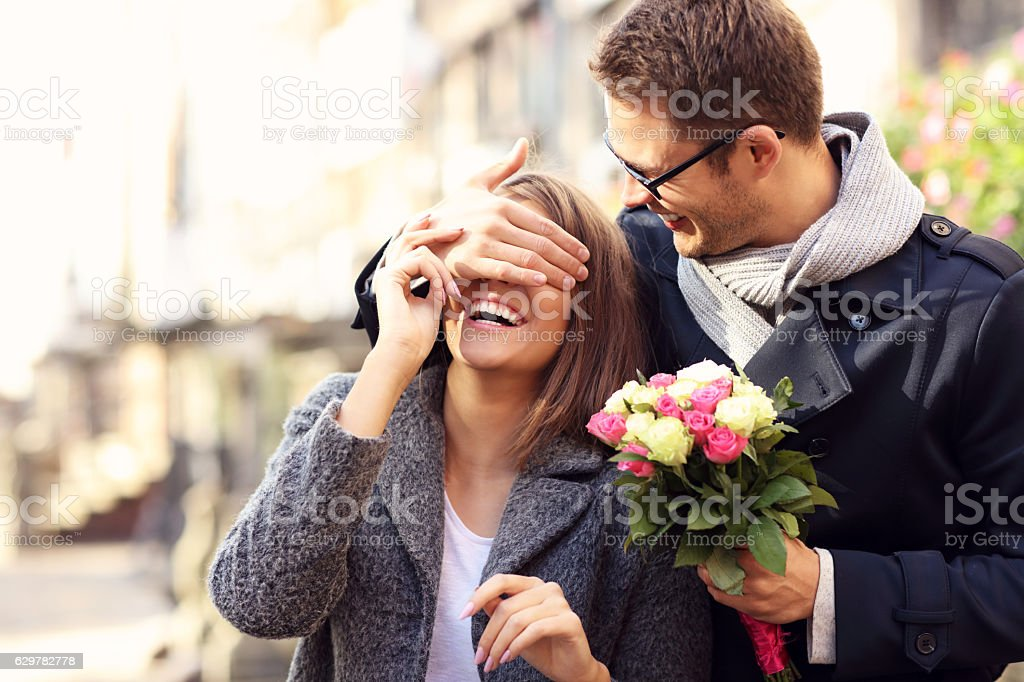 Young man surprising woman with flowers – Foto