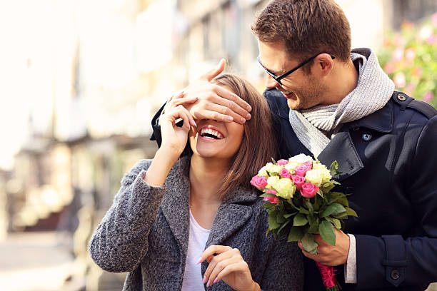 Young man surprising woman with flowers stock photo