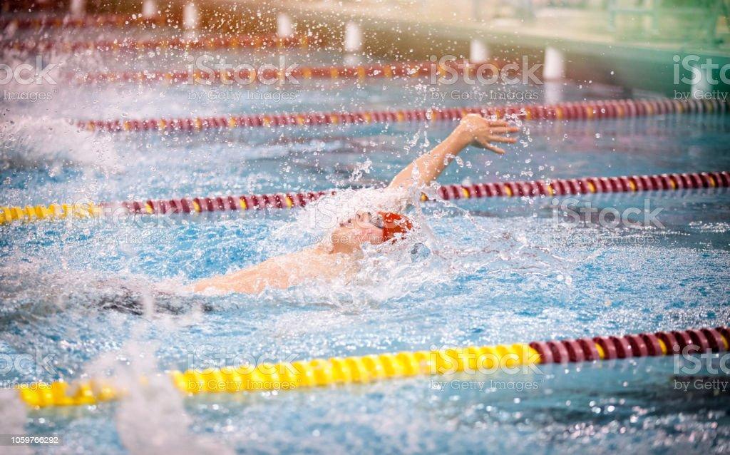 Young man swimming backstroke for boys high school varsity sports.