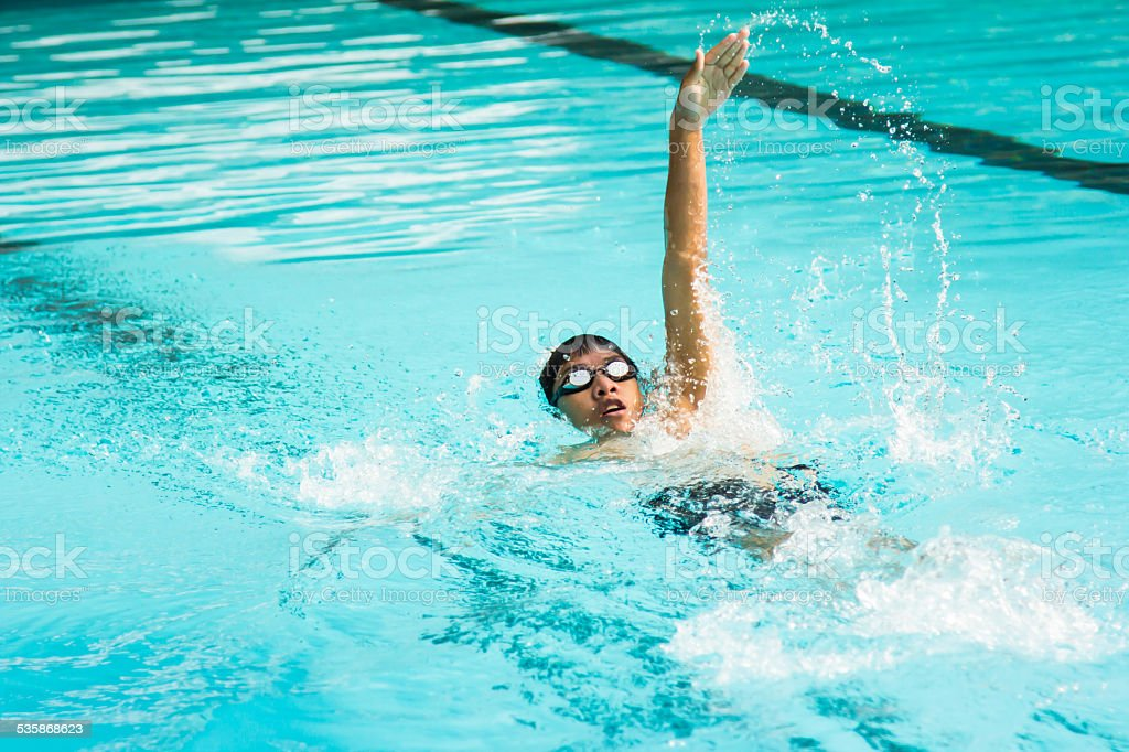 young man swimming in backstroke in a pool. stock photo