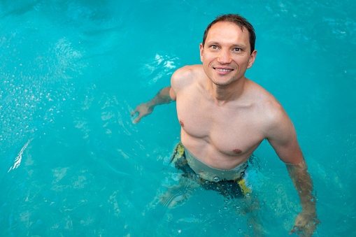 Young Man Swimming In Japanese Spa In Japan Onsen Hot Spring Pool With Colorful Blue Water Looking Up Happy Stock Photo Download Image Now Istock