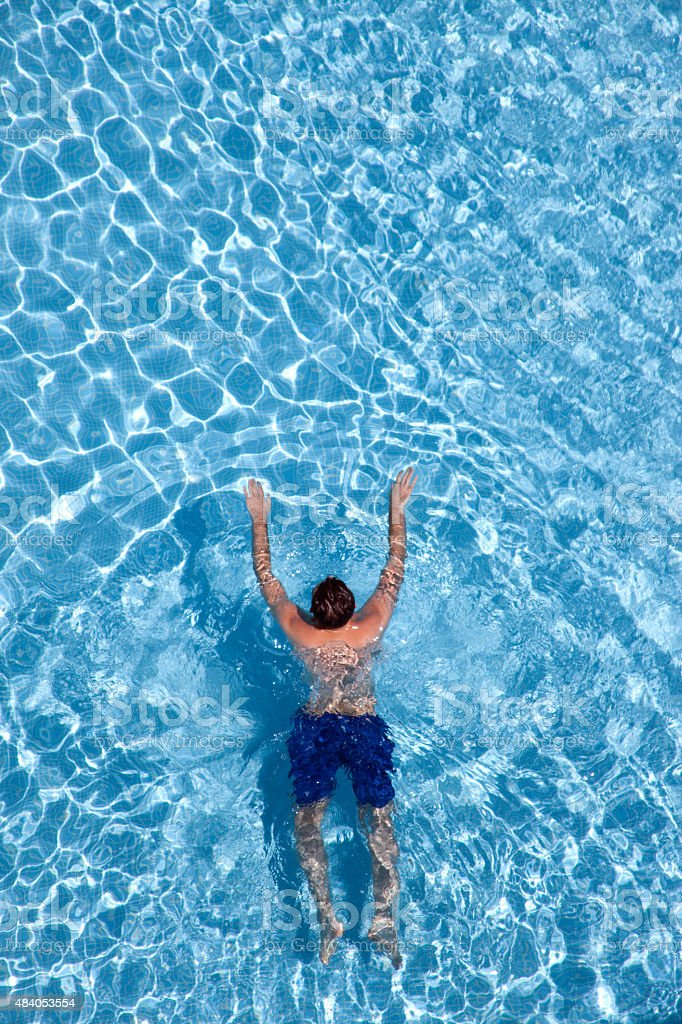 Young man swimming in the pool stock photo