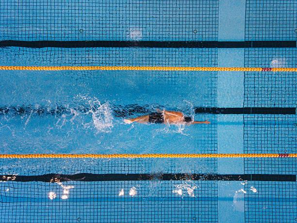 joven nadando vueltas en una piscina - natación fotografías e imágenes de stock