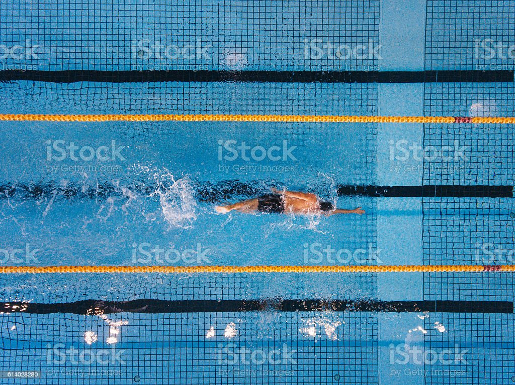 Young man swimming laps in a pool stock photo