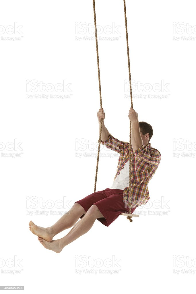 Young man swinging on swing rope royalty-free stock photo