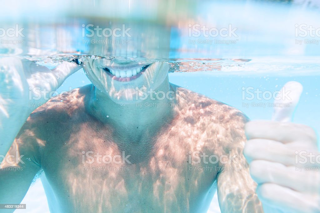 young man takes a call to smartphone underwater stock photo