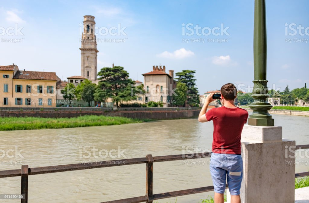 Young man takes a photo on a smartphone of the river in Verona, Italy stock photo