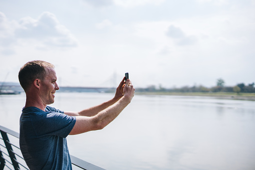 Young man takes photos on cellphone before morning run