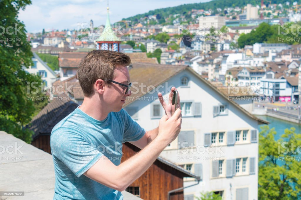 Young man takes smartphone photo of Zurich stock photo