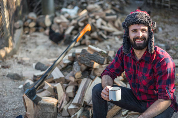 Young man taking a break as he cuts firewood Young bearded lumberman sitting on the wood logs with a cup of coffee lumberjack stock pictures, royalty-free photos & images