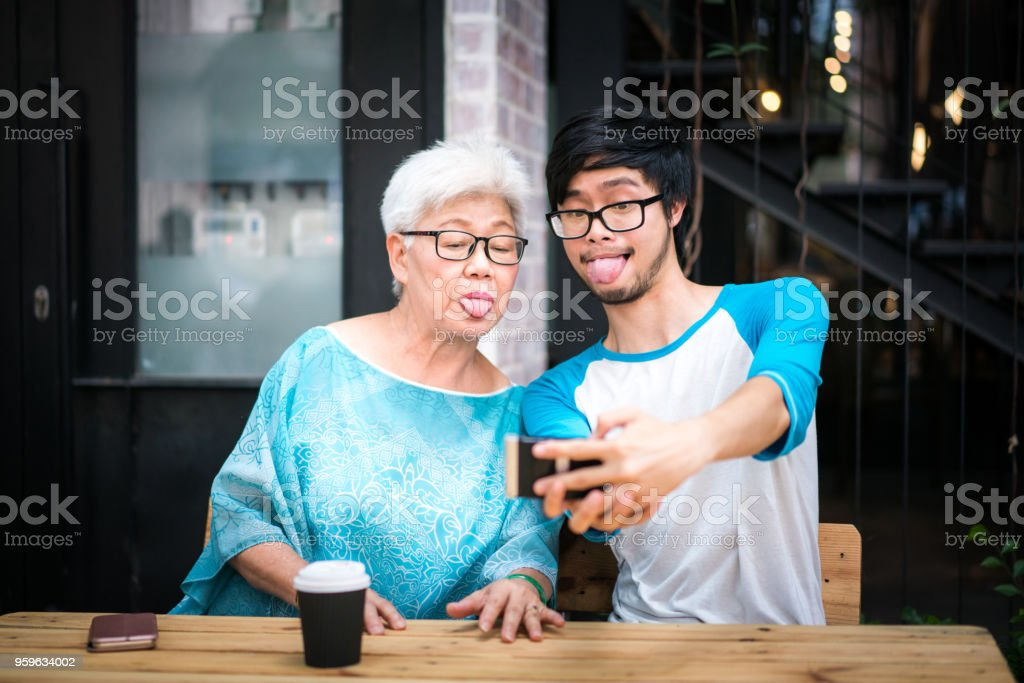 Young man taking a funny selfie with his grandmother stock photo